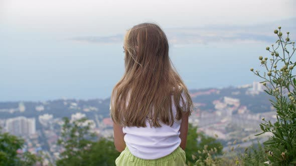 Thumbnail for Young Girl Sitting on Mountain Edge on City and Sea Landscape. Lonely Girl Enjoying Sea and City