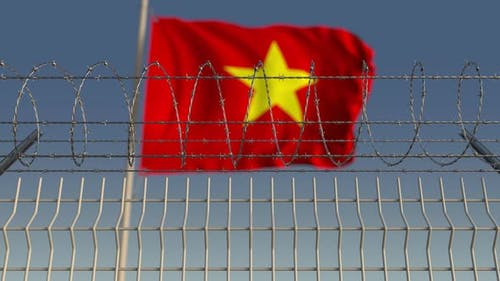 Waving Flag of Vietnam Behind Barbed Wire Fence