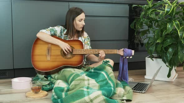 Caucasian brunette female learning to play acoustic guitar with online lessons. Learning guitar