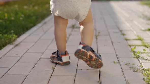 Thumbnail for Legs of Unrecognizable Toddler Walking on Footpath Outdoors