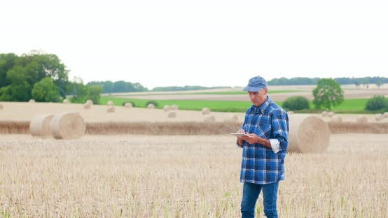 Thumbnail for Farmer Using Digital Tablet While Examining Field