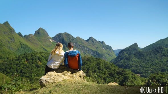 4K Hiking Couple Sit Down and Enjoy the Beautiful Mountain Scenery