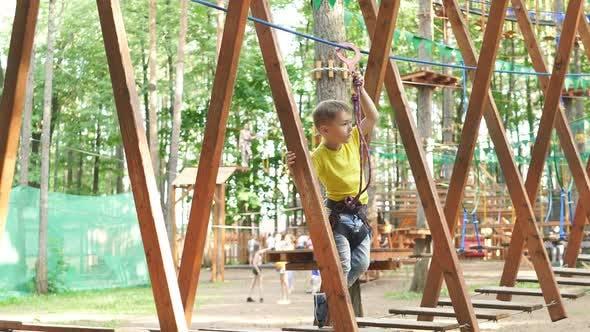 Tapferer kleiner Junge überwindet Hindernisse zwischen Bäumen und benutzt einen Sicherheits-Torso