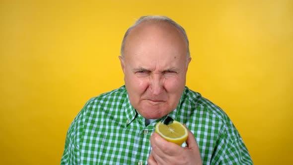 Cover Image for Senior Man Eating Sour Orange