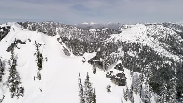 Thumbnail for Slow Rotating Aerial Of Cascade Mountain Range Summit With Cliffs Of Powder Snow In Washington State