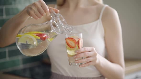 Young Woman Mixes Delicious Refreshing Drink with Lemon and Strawberry Slices in Glass Jug on Light
