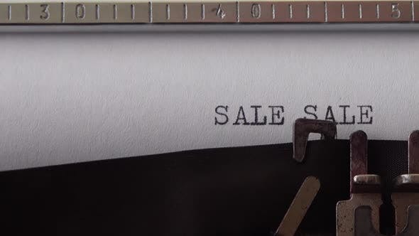 Typing words SALE SALE SALE !!! on retro typewriter. Close up.