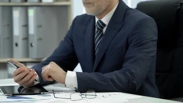 Thumbnail for Man in Business Suit Dialing, Talking on Cell Phone, Tablet and Glasses on Table