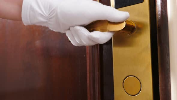 Cleaning and Hotel Concept. Close-up Shot of Maid in Gloves Opening Door Handle and Then Entering