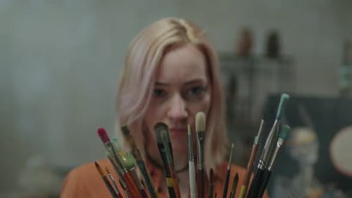 Inspirierte Malerin, die Pinsel im Innenbereich wählt