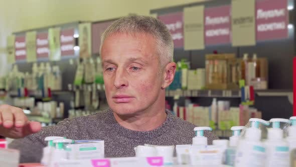 Thumbnail for Mature Man Shopping at the Drugstore, Examining Products on a Shelf