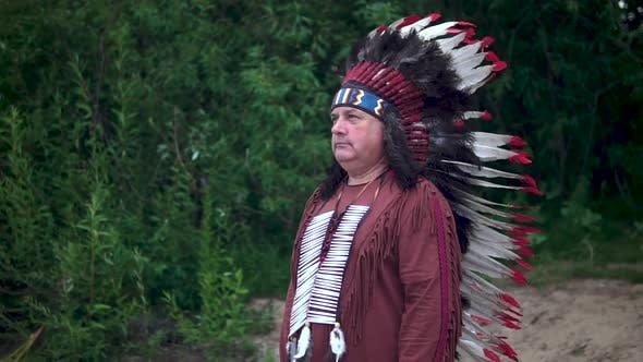 Thumbnail for Old Native American Indians Greets Raising His Hand. Stands Against the Background of the Forest