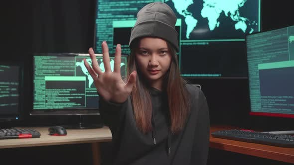 Young Asian Woman Hacker Showing Stop Hand, Code On Multiple Computer Screens