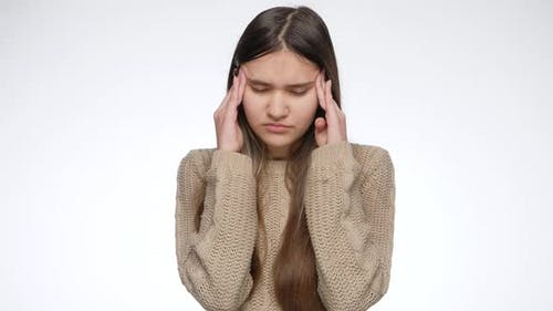 Frustrated Teenage Girl Suffering From Headache and Rubbing Her Head