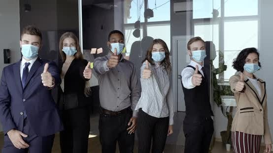 Thumbnail for Multi Ethnic Team of Young Ambitious Employees Wearing Face Masks, Posing Positive with Thumb Up