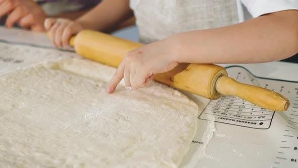 Little Girl in Kitchen Prepares Dough Rolling