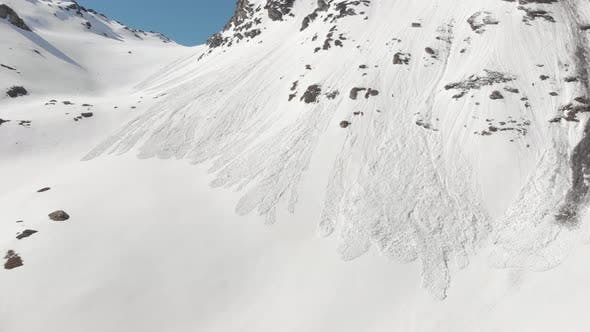 Thumbnail for Aerial: flying close to snow avalanche on mountain snowy slope reveals in springtime