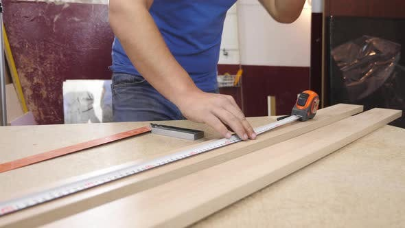Thumbnail for Carpenter measuring a piece of wood