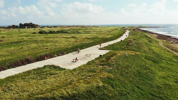 Thumbnail for Aerial Shot of Two Cyclists Riding Along Seashore Coastline and Pedestrians Walking on Beach Path