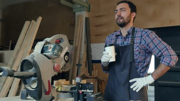 Thumbnail for The Carpenter Drink Coffee and Thinking About Something in Workshop Near Electric Saw.