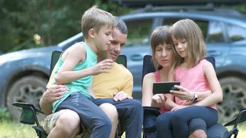 Young family sitting together at campsite browsing in mobile phone.