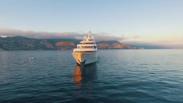 Front View of Large Super Yacht and Small Boat Underway. Luxury Super Yacht.