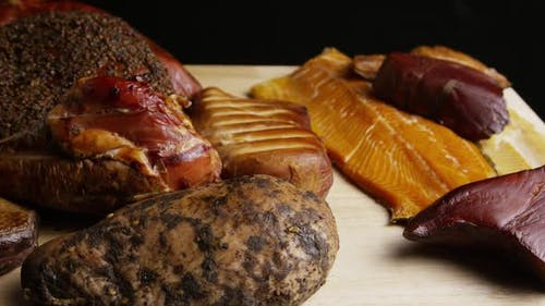 Rotating shot of a variety of delicious, premium smoked meats on a wooden cutting board - FOOD 055
