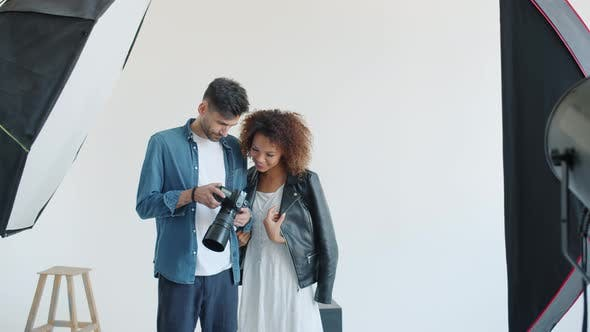 Model and Photographer Watching Photos on Digital Camera Smiling in Studio