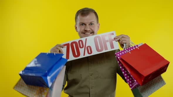 Happy Man Dancing, Celebrating, Showing Shopping Bags and Up To 70 Percent Off Inscription