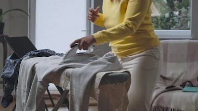 Unrecognizable African American Woman Having Fun Ironing Laundry Dancing at Home