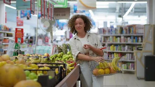 Housewife Holding Grocery Basket Picks Healthy Foods Fresh Fruit in Grocery Section of Supermarket