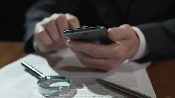 Cover Image for Business Expert Scrolling Financial News Feed on Smartphone, Working on Contract
