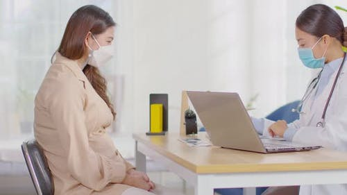 Smart Doctor wearing white coat with stethoscope talking to patient at hospital