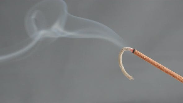 Close-up of burned  fragrant incense stick spreading smoke 4K 2160p 30fps UltraHD footage - Burning
