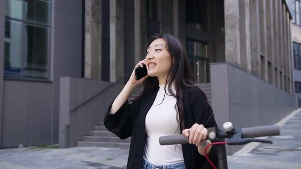 Thumbnail for Asian Girl Going with Her E-Scooter Near Beautiful Building and Talking on Phone