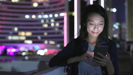 Thumbnail for Woman sending sms on cellphone in city at night