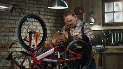 Grandfather and Grandson Repairing a Bicycle in a Garage