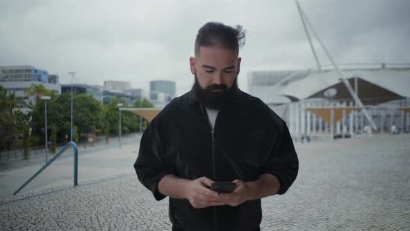 Thumbnail for Cheerful Young Bearded Man Using Smartphone