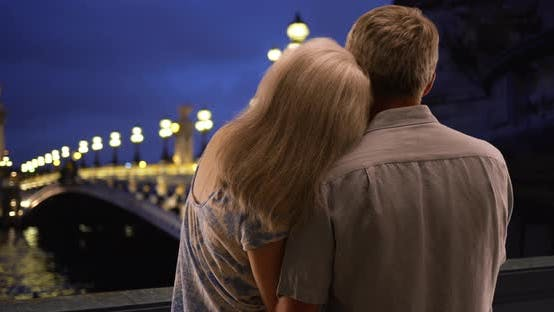 Thumbnail for Mature husband and wife gaze at the Seine in evening