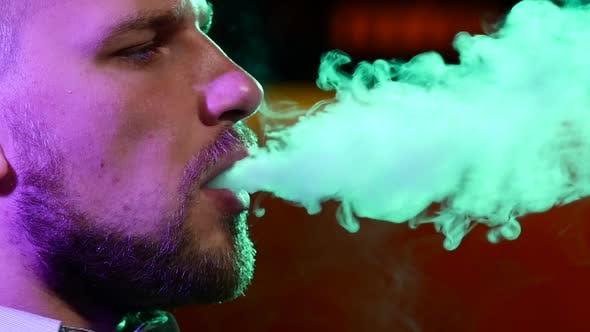 The Mouth of Man Smoking Shisha at Restaurant. Produces Smoke