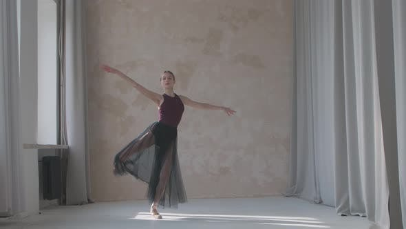 Flexible Ballerina in a Black Transparent Skirt Performs a Pirouette Movement By the Window