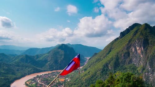 Nong Khiaw from the Pha Daeng mountain top national flag, dramatic sky, Laos