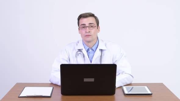 Thumbnail for Young Happy Handsome Man Doctor Greeting Against Wooden Table