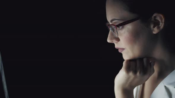Thumbnail for Portrait of a Young Woman Spending Time at the Computer in the Late Evening. Girl with Glasses