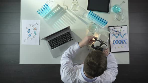 Lab Worker Looking Into Microscope, Recording Scientific Discovery on Laptop