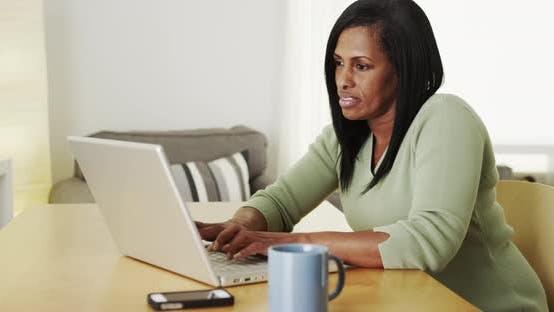 Thumbnail for Senior black woman working on laptop computer at desk
