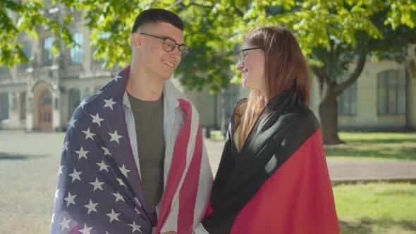 Thumbnail for Porträt von Happy Intelligent deutsche und amerikanische Studenten posieren auf University Campus Yard. Jung