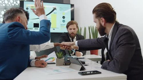 Multiracial Corporate Coworkers which Stacking Hands Together as a Sign Fruitful Collaboration