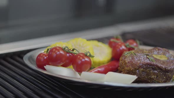 Thumbnail for The Plate with the Meat, Corn, Cherry Tomatoes, Lemongrass and Chili Pepper Lying on the Grill Close
