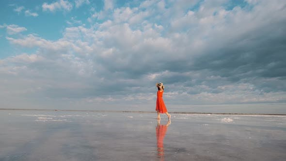 Thumbnail for Young Woman Traveler in a Hat and Sunglasses Walks Along a Salt Lake in Which the Sky and Clouds